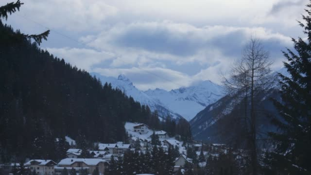 vídeos de stock, filmes e b-roll de time lapse sequence shows snowcovered mountain peaks moving clouds daylight changing to dusk above the town of davos switzerland on sunday jan 19... - moving activity
