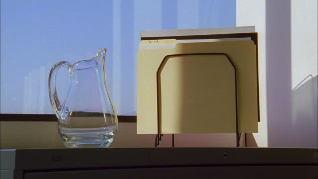 time lapse shadow passing over glass water pitcher and manila folders on desk - pitcher jug stock videos & royalty-free footage