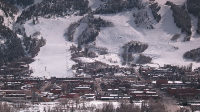 vidéos et rushes de time lapse shadows play on a snow covered mountain and a village below. - colorado