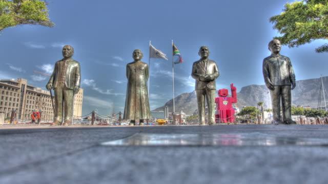 vídeos de stock, filmes e b-roll de time lapse shot across statues of albert luthuli, desmond tutu, f.w. de klerk and nelson mandelain noble square, cape town. - desmond tutu