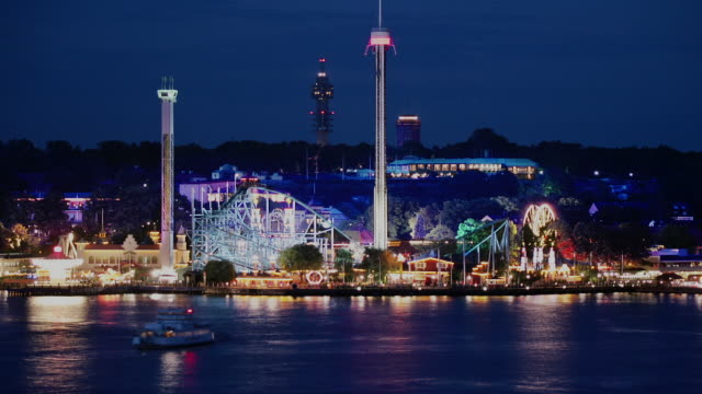 Time lapse shot across water of Grona Lund amusement park on waterfront at night / Stockholm, Sweden