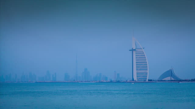 Time lapse shot from day to night of the Burj Al Arab hotel and the nearby skyscrapers of Dubai.