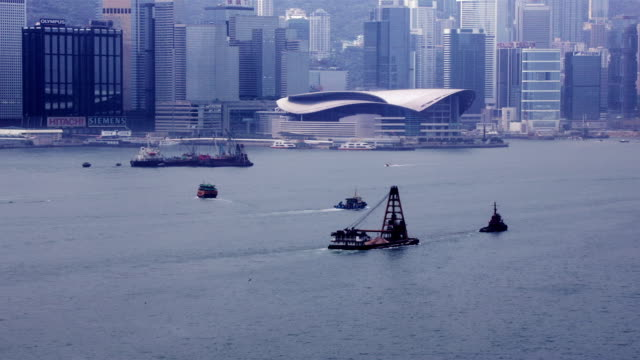 time lapse shot of boat traffic in victoria harbour passing hong kong convention and exhibition centre / hong kong - はしけ点の映像素材/bロール
