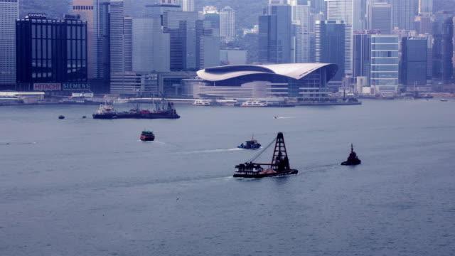vidéos et rushes de time lapse shot of boat traffic in victoria harbour passing hong kong convention and exhibition centre / hong kong - péniche commerciale