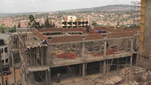 time lapse shot of builders working on a construction site in kigali. - brick stock videos & royalty-free footage