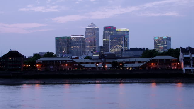 vídeos de stock e filmes b-roll de time lapse shot of canary wharf skyline lighting up as dusk turns to night / london, england - hsbc towers
