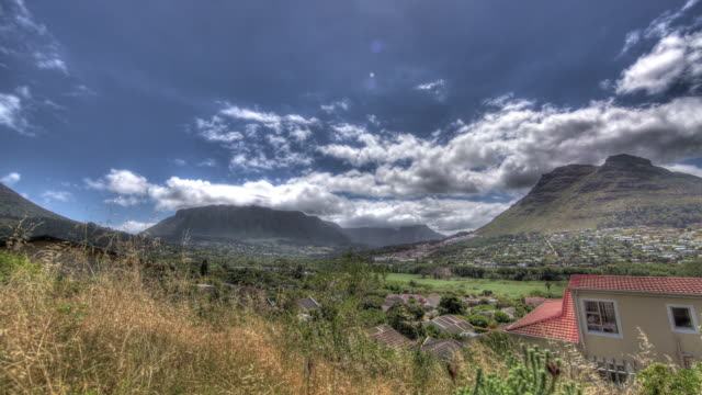 time lapse shot of clouds drifting across cape town the surrounding mountains. - 半島点の映像素材/bロール