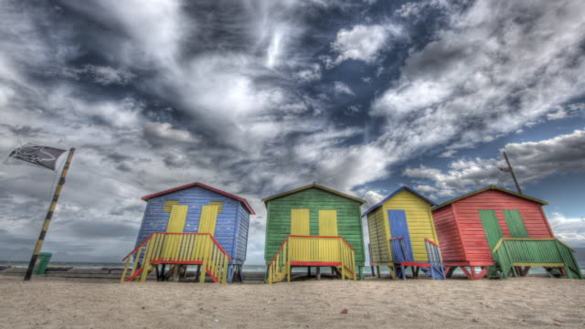 Time lapse shot of clouds drifting over brightly coloured beach huts on Camp Bay Beach, Cape Town.