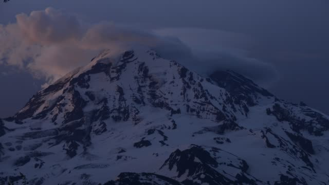 time lapse shot of clouds moving over snowcapped mountain at mount rainier national park - mt rainier national park stock videos & royalty-free footage