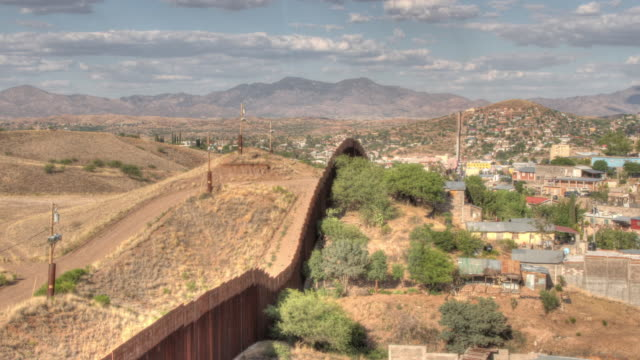 time lapse shot of clouds moving over the border fence between the usa and mexico near nogales. - omgivande mur bildbanksvideor och videomaterial från bakom kulisserna