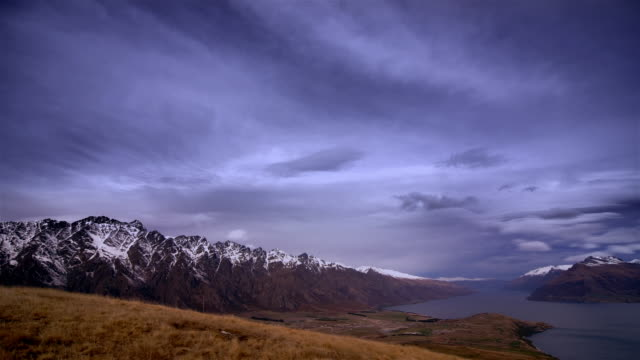 time lapse shot of clouds passing over the remarkables and lake wakatipu / queenstown, south island, new zealand - queenstown stock videos & royalty-free footage