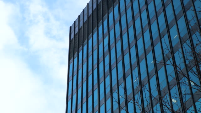 time lapse shot of clouds reflecting off the windows of an office block near london's euston road. - office block exterior stock-videos und b-roll-filmmaterial