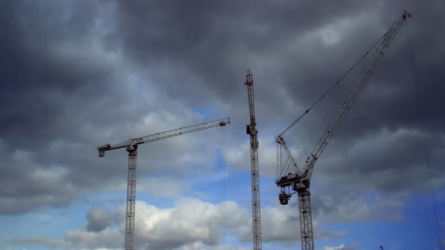 Time lapse shot of construction cranes in motion.
