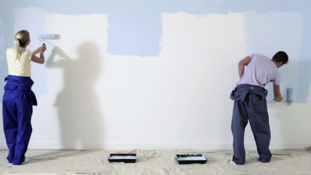 time lapse shot of couple painting a wall - paint roller stock videos & royalty-free footage