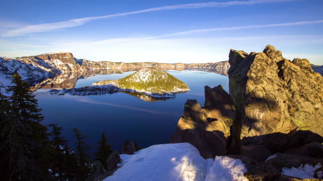 time lapse shot of crater lake amidst mountains and snow against sky from day to sunset - オレゴン州クレーター湖点の映像素材/bロール