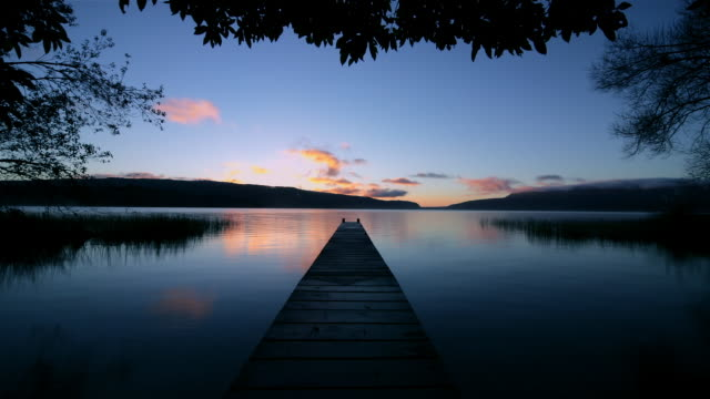 time lapse shot of dock extending into still waters of lake tarawera and clouds passing over horizon on winter morning / rotorua, new zealand - ruhige szene stock-videos und b-roll-filmmaterial