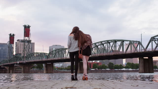 Time lapse shot of female friends standing on pier over Willamette River against cloudy sky during sunset