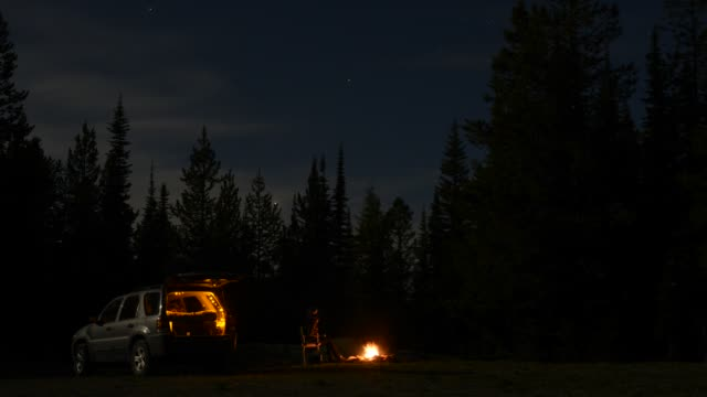 time lapse shot of female tourist sitting by bonfire outside sports utility vehicle against trees at lake shastina during night - camping点の映像素材/bロール