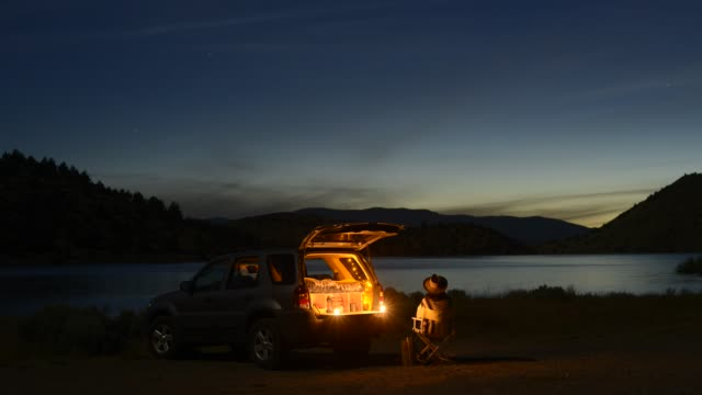 vídeos de stock e filmes b-roll de time lapse shot of female tourist sitting on camping chair outside sports utility vehicle by lake shastina during night - parado