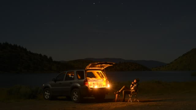 vídeos y material grabado en eventos de stock de time lapse shot of female tourist sitting on camping chair outside illuminated sports utility vehicle by lake shastina during night - inmóvil