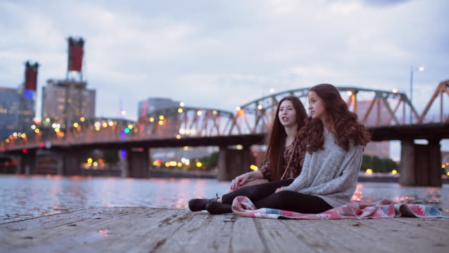 Time lapse shot of friends singing while sitting on pier over Willamette River