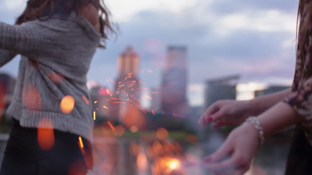 Time lapse shot of happy female friends burning sparklers by Willamette River against cloudy sky