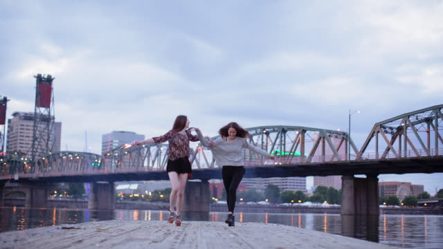 Time lapse shot of happy friends holding hands and running on pier over Willamette River against cloudy sky
