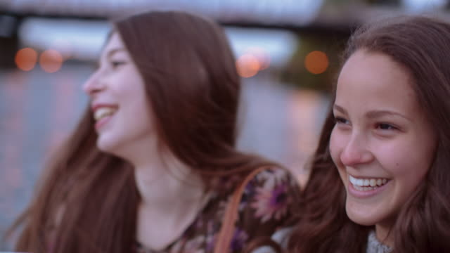 Time lapse shot of happy friends talking while sitting by Willamette River during sunset