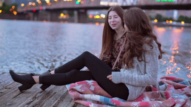 Time lapse shot of happy friends talking while sitting on pier over Willamette River during sunset