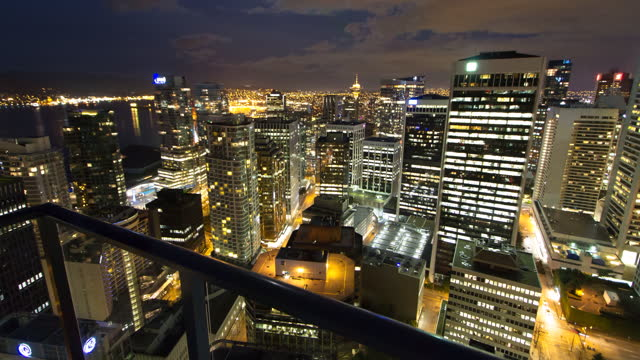 time lapse shot of illuminated tall buildings seen through balcony against cloudy sky at night - vancouver, canada - balcony stock videos & royalty-free footage
