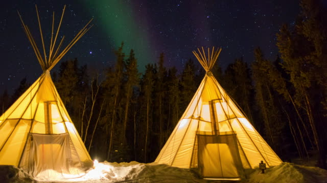 time lapse shot of illuminated teepees on snow by trees against sky at night - northwest territories, canada - group of objects stock videos & royalty-free footage