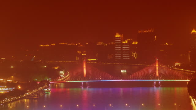 time lapse shot of illuminated tourist cruise boat passing under illuminated suspension bridge on pearl river in guangzhou, china - spoonfilm stock-videos und b-roll-filmmaterial