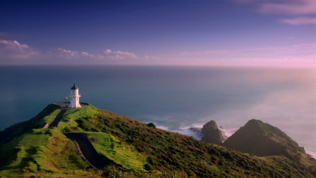Time lapse shot of lighthouse on promontory with waves crashing against coast / Cape Reinga, New Zealand
