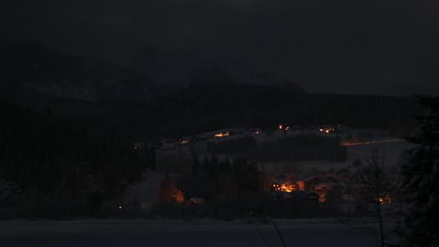 Time lapse shot of lightning illuminating village of Untersee on shore of Hallstattersee on winter night / Austria