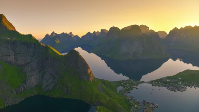 Tijd lapse schot van Noorse vissersdorp op de eilanden van de Lofoten in Noorwegen. Dramatische zonsondergang wolken die bewegen over steile bergtoppen.