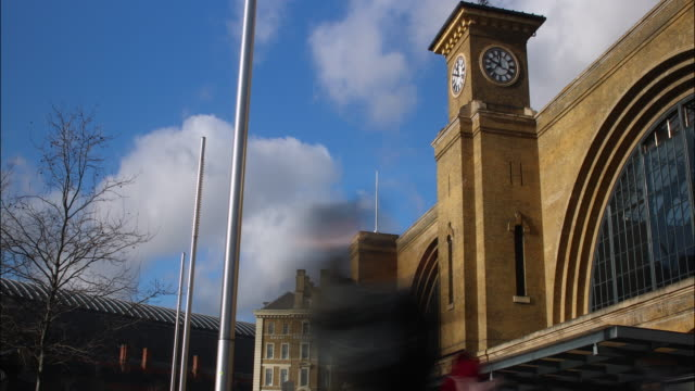 Time lapse shot of pedestrians moving past the exterior of Kings Cross Station in London.