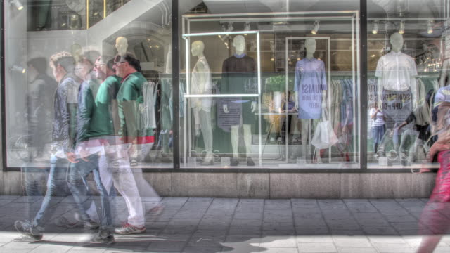 Time lapse shot of pedestrians walking past a shop window in Stockholm.