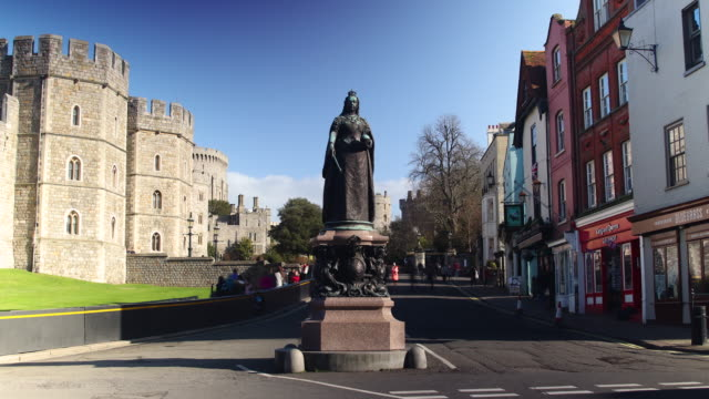 Time lapse shot of pedestrians walking past a statue of Queen Victoria at Windsor Castle.