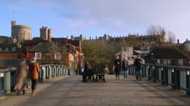 time lapse shot of people crossing a pedestrian bridge near windsor castle. - windsor castle stock videos and b-roll footage