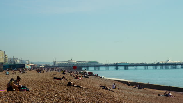 time lapse shot of people relaxing on brighton beach. - sunbathing stock videos & royalty-free footage