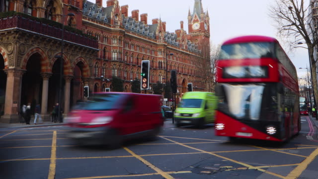 vídeos de stock e filmes b-roll de time lapse shot of people using a pedestrian crossing near the st pancras hotel on london's euston road. - time lapse de trânsito