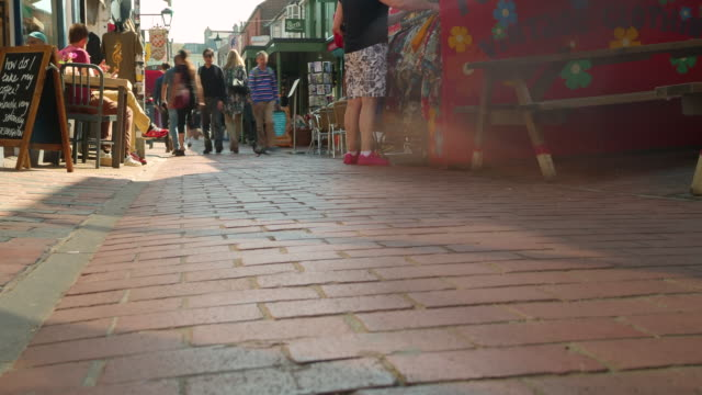 stockvideo's en b-roll-footage met time lapse shot of people walking along kensington garden's in brighton's famous north lanes. - mid adult men