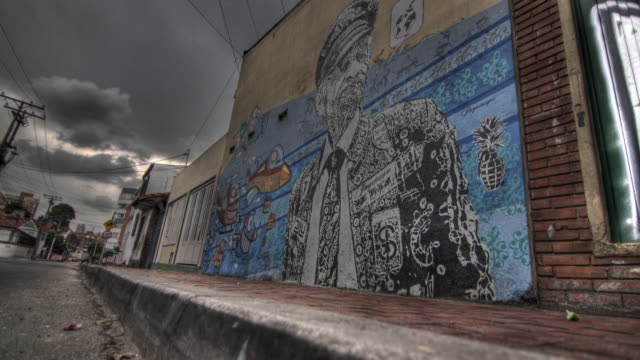 time lapse shot of people walking past a large mural painted on the side of a building in bogota. - bogota stock videos & royalty-free footage