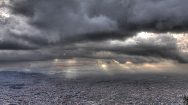 Time lapse shot of rays of light breaking through storm clouds over the city of Bogota.
