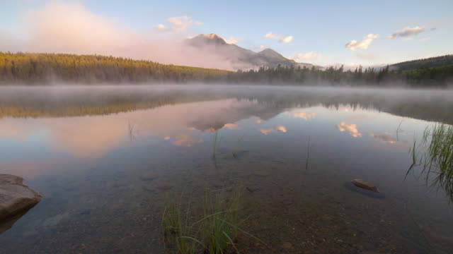 time lapse shot of reflection on pyramid lake with fog at national park against sky - jasper national park, canada - jasper national park stock videos & royalty-free footage