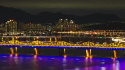 Time lapse shot of Seoul cityscape with Han River and traffic on expressway at night, South Korea