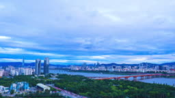 Time lapse shot of Seoul cityscape with Lotte Tower, Han River and traffic on expressway at twilight time, South Korea