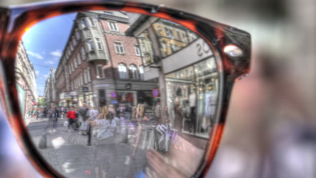 time lapse shot of shoppers in stockholm, reflected in the lens of a pair of mirrored sunglasses. - spectacles stock videos & royalty-free footage