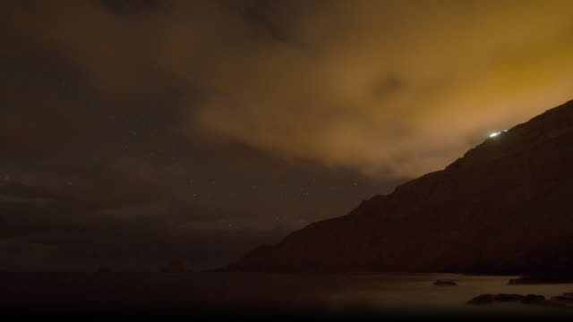 vídeos de stock e filmes b-roll de time lapse shot of stars and clouds moving over the coast of el hierro. - data