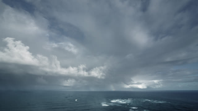 time lapse shot of storm clouds drifting over water / new zealand - storm stock videos & royalty-free footage
